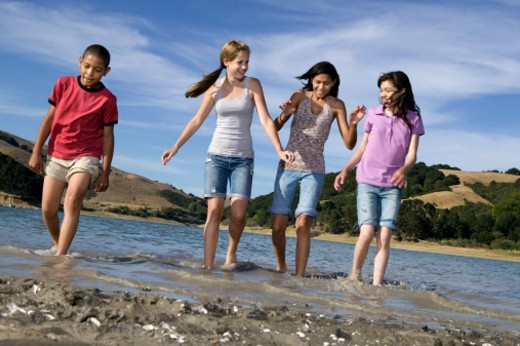 Stock Photo: 1527R-1168067 Group of children (11-14 years) playing in lake, low section