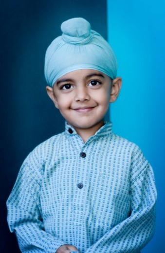Portrait of Sikh boy (4-5) in turban, smiling : Stock Photo