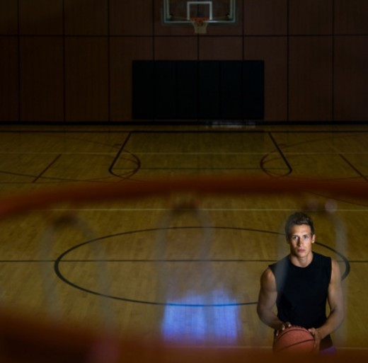 Man with basketball in basketball court in gym, portrait, elevated view : Stock Photo