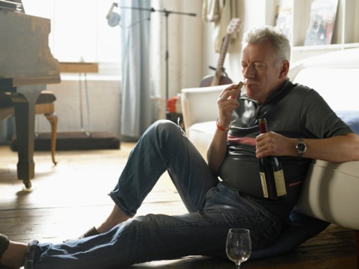 Mature man sitting on floor, smelling wine cork : Stock Photo