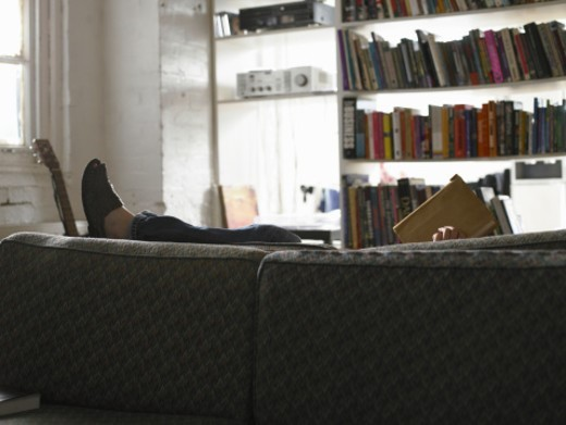 Man lying down on sofa, reading book, side view : Stock Photo