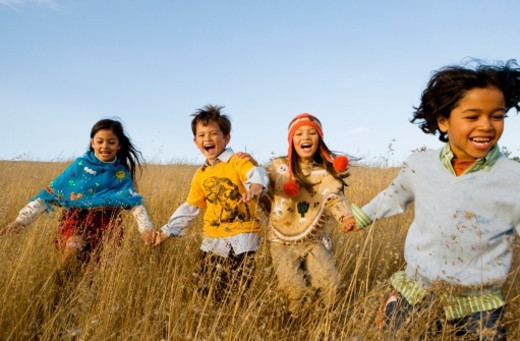 Four kids (6-8) running through field : Stock Photo