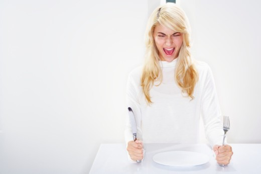 Stock Photo: 1527R-1169111 Young woman in front of empty plate, screaming