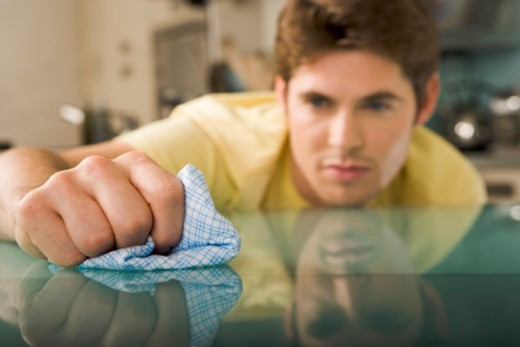Stock Photo: 1527R-1169412 Young man wiping glass table with cloth (focus on hand and cloth)
