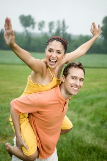 Man giving woman piggyback in field, portrait : Stock Photo