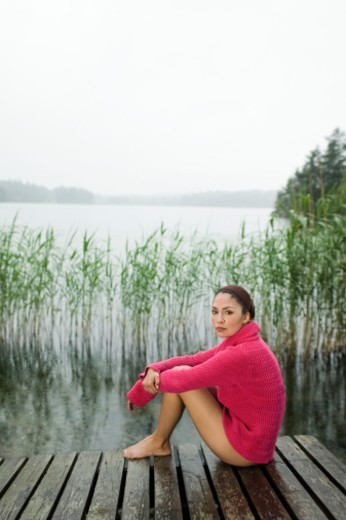 Stock Photo: 1527R-1169742 Young woman sitting on jetty, portrait