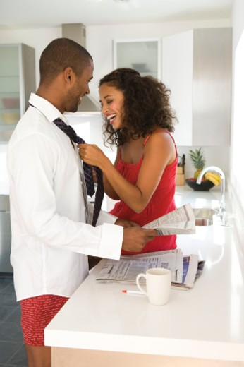 Stock Photo: 1527R-1169773 Young couple flirting in kitchen