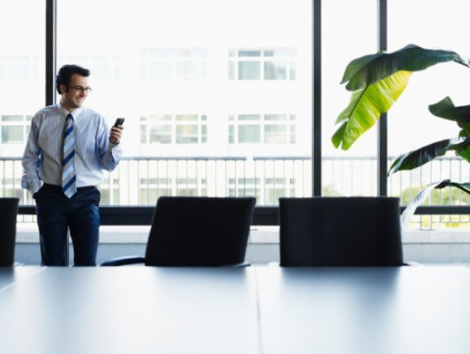 Young businessman using mobile phone in conference room : Stock Photo