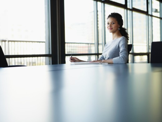 Stock Photo: 1527R-1170320 Portrait of businesswoman reading papers at conference table