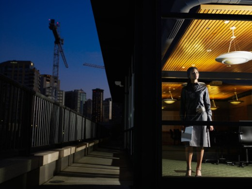 Businesswoman looking out of window of conference room at night : Stock Photo