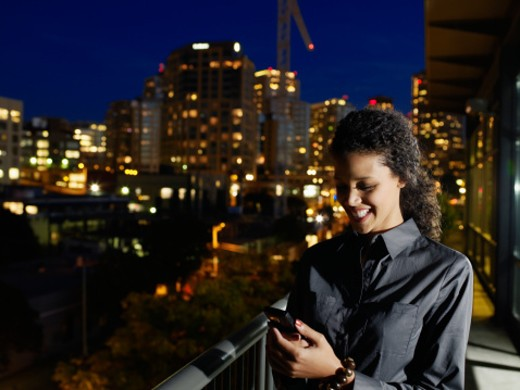 Businesswoman using mobile phone on balcony at night : Stock Photo