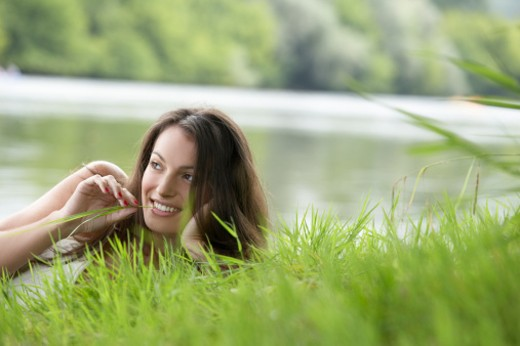 Young woman lying on meadow by river, chewing blade of grass (surface level) : Stock Photo