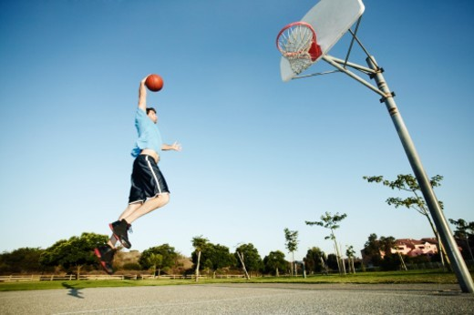Man slamdunking basketball on outdoor court : Stock Photo