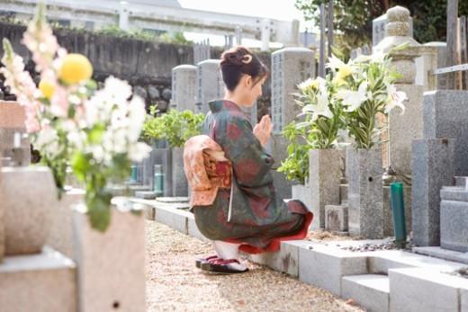 Japan, Kyoto, woman in kimono praying in cemetery : Stock Photo