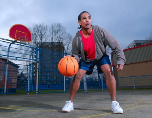 Stock Photo: 1527R-1172924 Young man playing basketball, outdoors