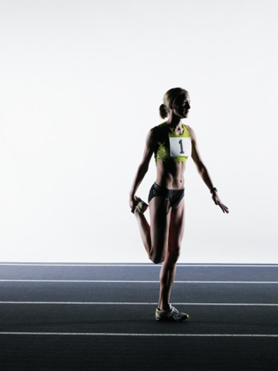 Stock Photo: 1527R-1173473 Female runner stretching on track