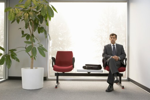 Mature businessman sitting in lobby, hands clasped : Stock Photo