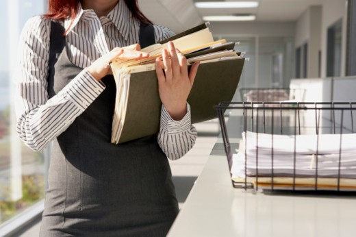 Young businesswoman looking through documents and files, mid section : Stock Photo