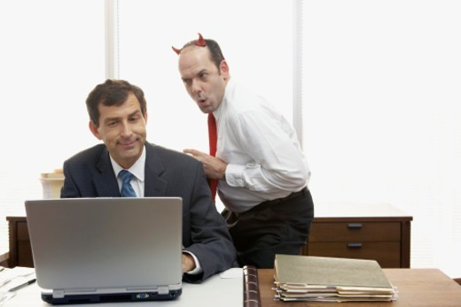 Man with devil horns standing behind mature businessman using laptop : Stock Photo