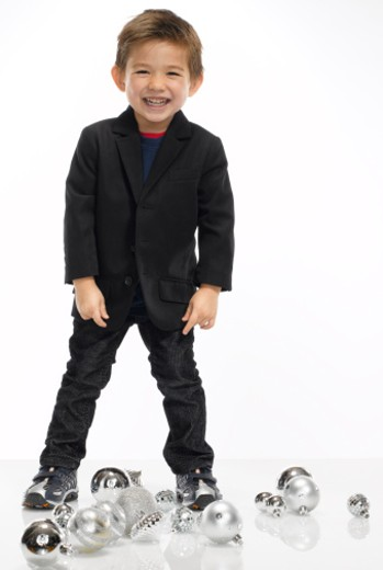 Boy (2-3) standing by Christmas ornaments, studio portrait : Stock Photo
