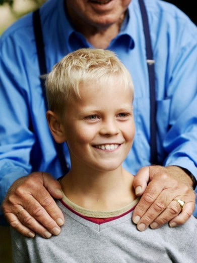 Boy (10-11), grandfather behind with hands on his shoulders : Stock Photo