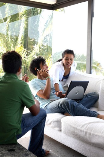 Teenagers (15-17) using cell phone and laptop in living room : Stock Photo