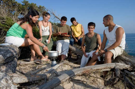 Group of young people cooking at camp stove : Stock Photo