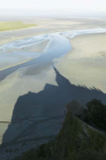 France, Normandy, shadow of Mont Saint-Michel Abbey on sand at low tide : Stock Photo