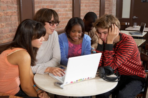 Group of people sitting at caf? table using laptop, smiling : Stock Photo