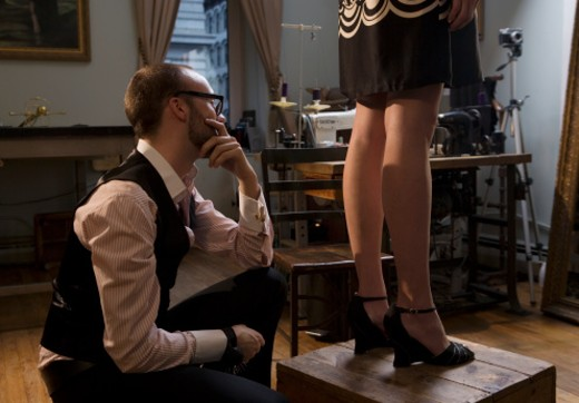 Tailor looking at female model's dress : Stock Photo