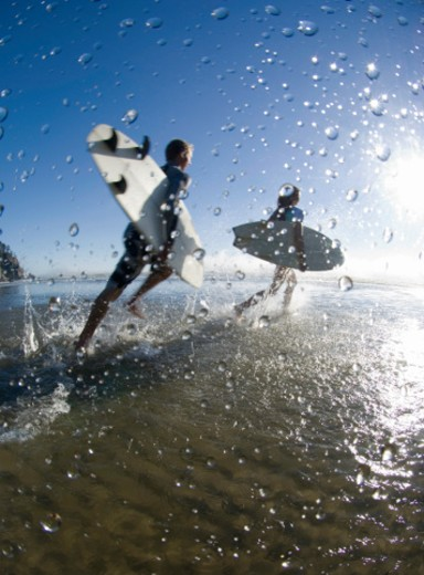 Stock Photo: 1527R-1176578 Two people running into ocean with surfboard, rear view