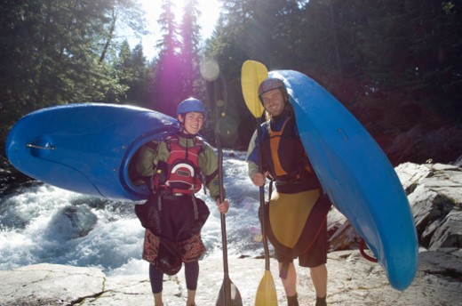 Stock Photo: 1527R-1176582 Two people carrying kayaks on shore