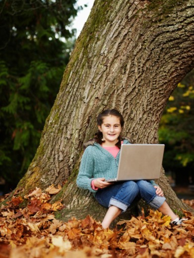Girl (8-9) using laptop by tree in woodland, portrait : Stock Photo