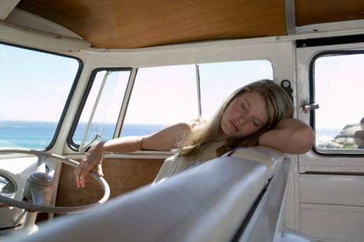 Young woman sleeping in camper van : Stock Photo