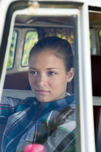 Young woman sitting in camper van, view through windscreen : Stock Photo
