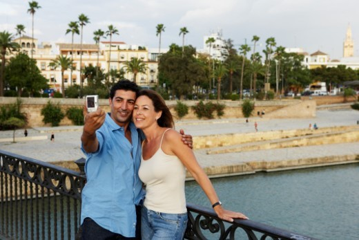 Couple taking picture on bridge, Guadalquivir River, Seville, Spain : Stock Photo