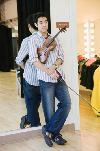 Young man with violin standing outside dressing room : Stock Photo