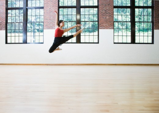 Female ballerina jumping mid-air, arms outstretched : Stock Photo