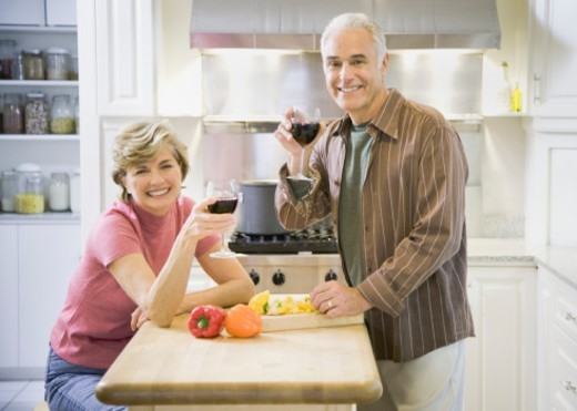 Senior couple with wine glasses in kitchen, smiling, portrait : Stock Photo