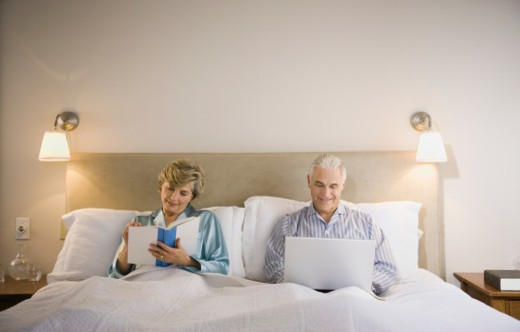 Senior couple on bed, reading and using laptop, smiling : Stock Photo