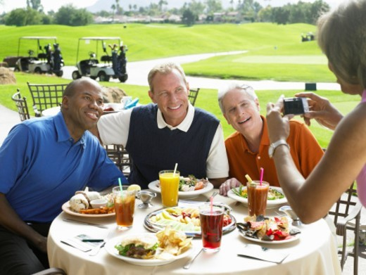 Stock Photo: 1527R-1179486 Woman photographing three men eating lunch at golf course