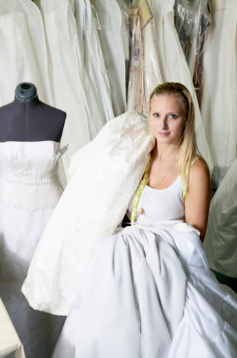 Young fashion designer carrying wedding dress, portrait : Stock Photo
