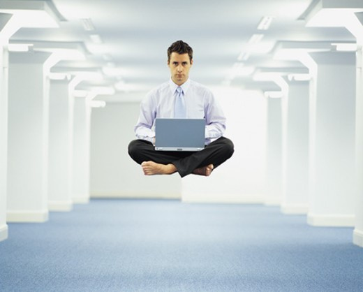 Portrait of a Businessman Levitating and Using a Laptop in an Open Plan Office : Stock Photo