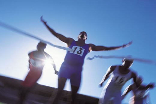 Stock Photo: 1527R-1182464 Four Athletes Sprinting to the Finishing Line