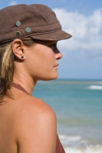 Young woman wearing hat at ocean : Stock Photo