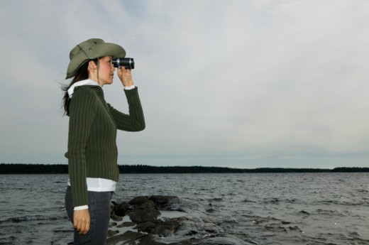 Stock Photo: 1527R-1184292 Woman standing be sea, looking through binoculars