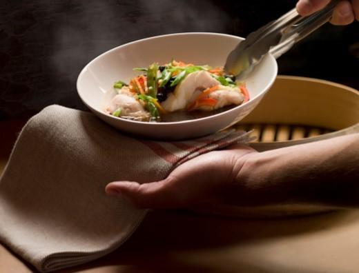 Woman serving steaming white fish in broth, close-up of hands : Stock Photo