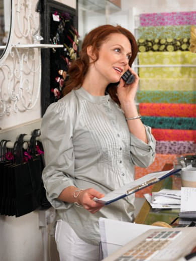 Young woman, owner of gift shop, talking on mobile phone behind checkout counter, holding clipboard : Stock Photo