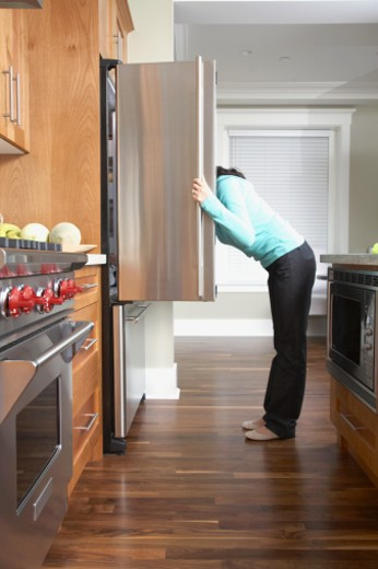 Stock Photo: 1527R-1185882 Woman looking inside fridge