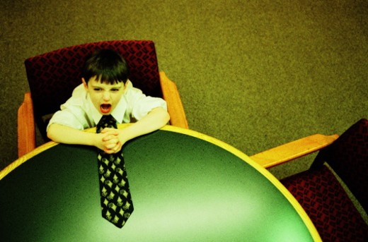 Stock Photo: 1527R-1186996 Boy (4-6) siting at conference table, elevated view (cross-processed)